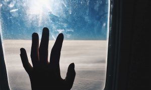 hand on window above clouds