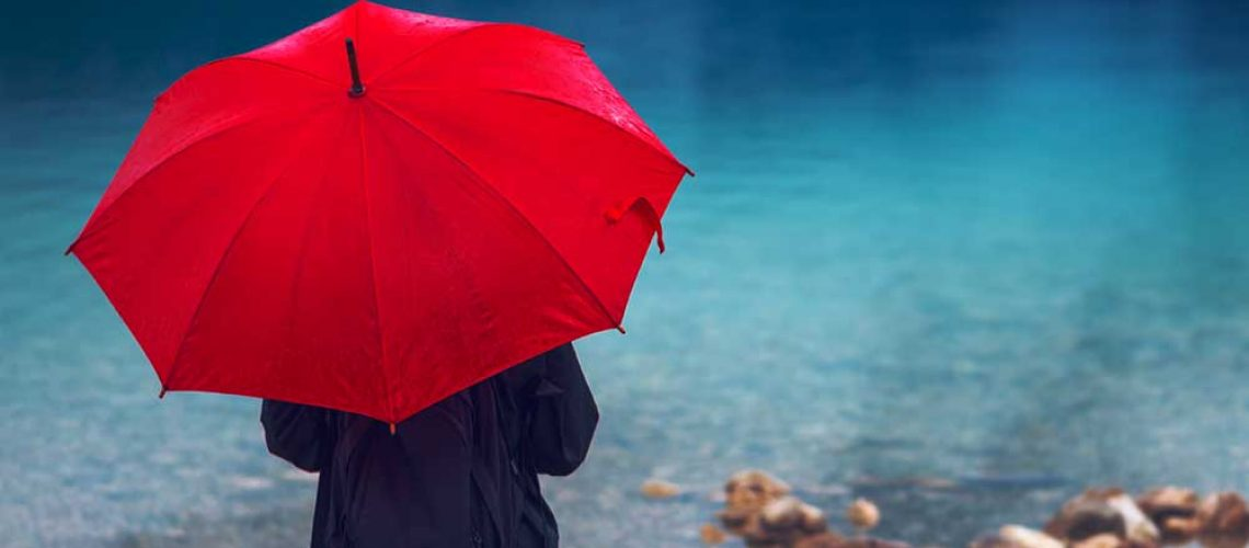 person standing by sea with red umbrella